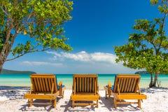 Zonlanterfanters op het strand die uit aan een paradijsoverzees kijken Stock Afbeelding