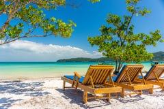 Zonlanterfanters op het strand die uit aan een paradijsoverzees kijken Royalty-vrije Stock Foto