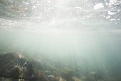 Zonlicht die door de oceaanoppervlakte glanzen en de zeebedding, met inbegrip van witte zand en Granietrotsen bereiken stock foto's
