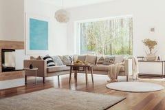 Zonlicht die door een groot venster in een wit en beige woonkamerbinnenland komen met fruitkommen op een houten lijst royalty-vrije stock afbeeldingen