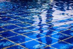 Zonlicht die weg van een duidelijke blauwe tegelpool nadenken op een de zomerdag Stock Afbeelding