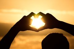 Zonlicht door de handen van de hartvorm stock afbeelding