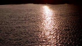 Zonlichtbezinning in water in de zonsondergang, overzeese golven met zon het optekenen stock videobeelden