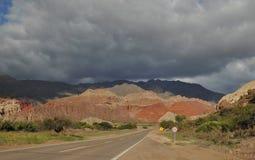 Zonlichtverlichting omhoog de rode gekleurde rotsen met zich het donkere wolken verzamelen Stock Fotografie