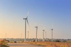 Zonne-energiepanelen en windturbine in zonsondergang Stock Fotografie