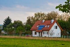 Zonnebatterij op het dak van een landelijk huis onder een blauwe zonnige hemel zonne-energie, alternatieve elektriciteit stock foto's