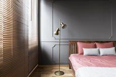 Zonneblinden en gouden lamp in donker en elegant slaapkamerbinnenland met royalty-vrije stock fotografie
