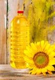 Zonnebloem en een fles plantaardige olie stock foto's