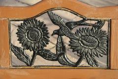 Zonnebloemen en een vogel, gesmeed van metaal in een oud houten kader stock foto
