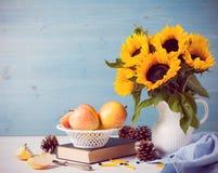 Zonnebloemenboeket in witte vaas met appelen stock foto