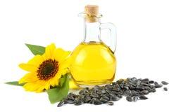 Zonnebloemolie in glaskruik, zaden en bloem op witte achtergrond wordt geïsoleerd die royalty-vrije stock afbeeldingen