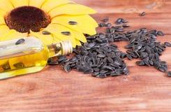 Zonnebloemzaden, een fles olie stock afbeeldingen