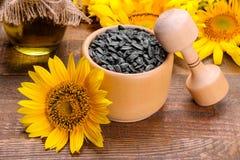 Zonnebloemzaden in een houten verbrijzeling en gele zonnebloemen op een bruine houten achtergrond stock foto's