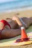 Zonnebrandolie en zonnebril op strand Stock Foto