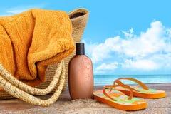 Zonnebrandolie, met handdoek bij het strand Stock Foto