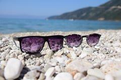 Zonnebril dichtbij overzees, strand stock afbeeldingen