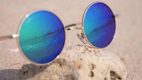 Zonnebril die op het zand op het strand liggen De zonnebril wijst op het overzees, de zon, de hemel, het strand 4k, langzame moti stock footage