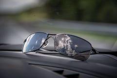 Zonnebril die zich op autostreepje tijdens een wegreis bevinden met wolkenbezinningen royalty-vrije stock foto's