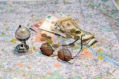 Zonnebril, een glasbol en een geld op een achtergrond van de toeristenkaart Het concept van het toerisme royalty-vrije stock afbeelding