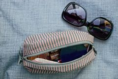 Zonnebril en een open kleine gestreepte zak op grijze doek Royalty-vrije Stock Afbeeldingen