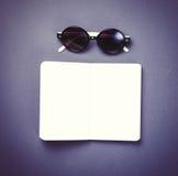 Zonnebril en klassiek notitieboekje op violette achtergrond Royalty-vrije Stock Foto's