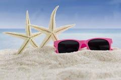 Zonnebril en overzeese sterren bij strand Stock Foto