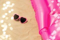 Zonnebril en roze zwemmende matras op strand royalty-vrije stock foto's