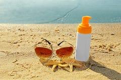 Zonnebril, lotion en zeesterren op zand Stock Afbeeldingen