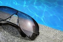 Zonnebril naast een pool Stock Fotografie