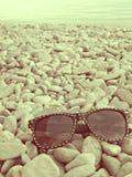 Zonnebril op de kust van het overzees in uitstekende kleuren Stock Foto's