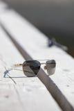 Zonnebril op een pier.GN stock afbeelding