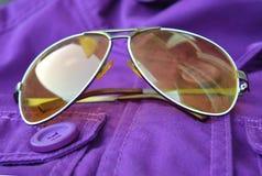 Zonnebril op het purpere jasje Stock Afbeeldingen