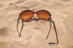 Zonnebril op het zand Stock Foto