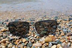Zonnebril op Kleurrijke Stenen bij de Water` s Rand stock afbeelding