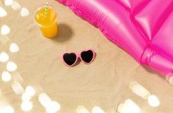 Zonnebril, sap en poolmatras op strandzand stock afbeelding