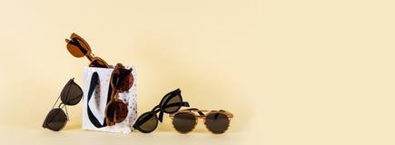 Zonnebrilverkoop De zomer biedt verkoop-uit aan Zonnebril in houten kader op gele achtergrond De ruimte van het exemplaar Voor ba stock foto
