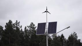 Zonnepanelen en een kleine windturbine voor de productie van milieuvriendelijke energie stock footage