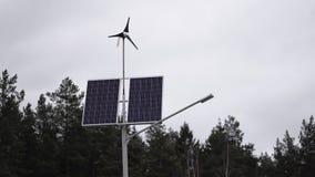 Zonnepanelen en een kleine windturbine voor de productie van milieuvriendelijke energie stock video