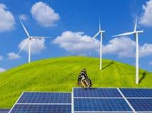 Zonnepanelen en vlinder met windturbines op grasheuvel en blauwe hemel Stock Foto's