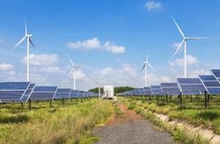 Zonnepanelen en windturbines in krachtcentrale groene energie vernieuwbaar met blauwe hemelachtergrond royalty-vrije stock foto's