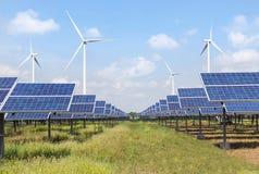 Zonnepanelen en windturbines in krachtcentrale groene energie vernieuwbaar met blauwe hemelachtergrond stock fotografie