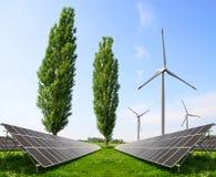 Zonnepanelen met windturbines op weide Stock Fotografie