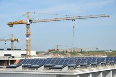 Zonnepanelen op de bovenkant van een gebouw met torenkranen stock fotografie