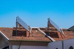 Zonnepanelen op rood betegeld dak van flatgebouw royalty-vrije stock foto's