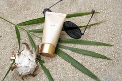 Zonnescherm, glazen, shell, palmblad op zand stock foto