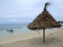 Zonnescherm op een strand in bewolkt weer Stock Afbeeldingen