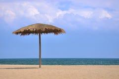 Zonnescherm op strand met blauwe hemel en witte wolk Royalty-vrije Stock Foto's