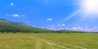 Zonneschijn op berg en blauwe hemel met groene weide Royalty-vrije Stock Foto's