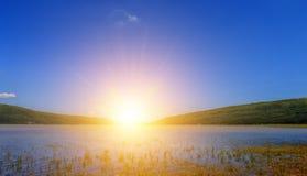 Zonneschijn op berg en blauwe hemel over rivier Royalty-vrije Stock Foto
