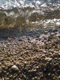 Zonneschijnfonkelingen op golven over een kiezelsteenkust royalty-vrije stock fotografie